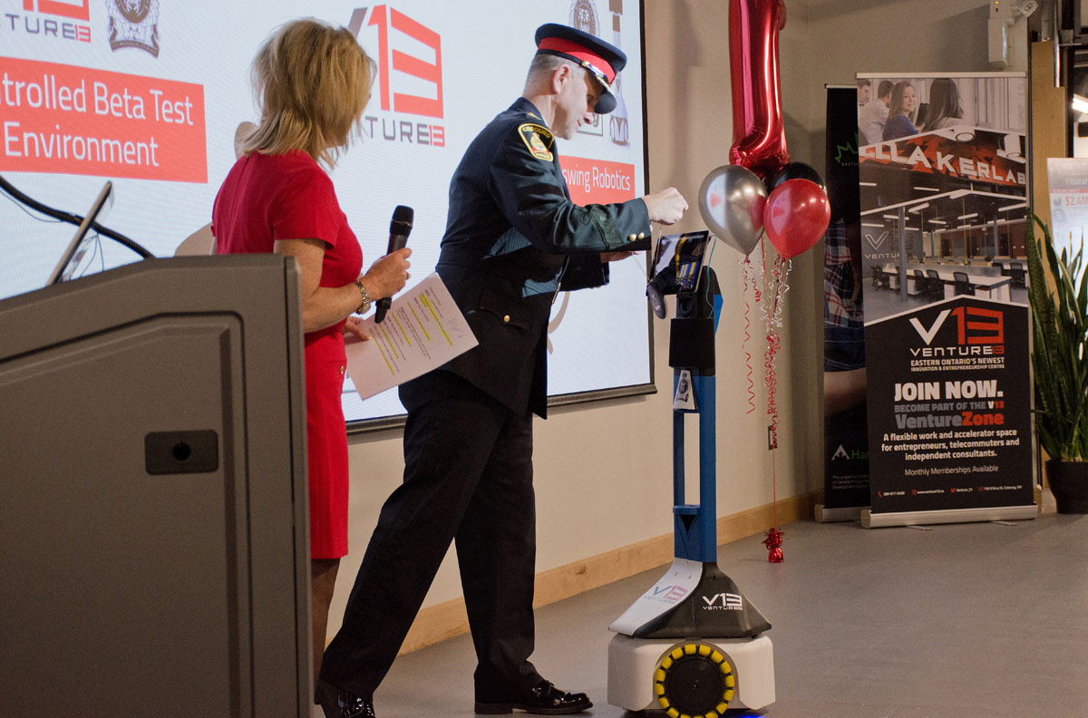 Acting Chief of police Paul Vandegraaf giving robot a badge