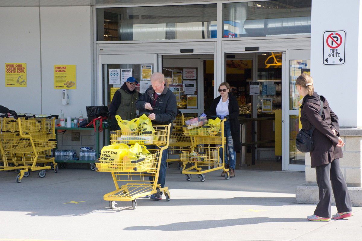 Man with blue cap is policing entrance at No Frills